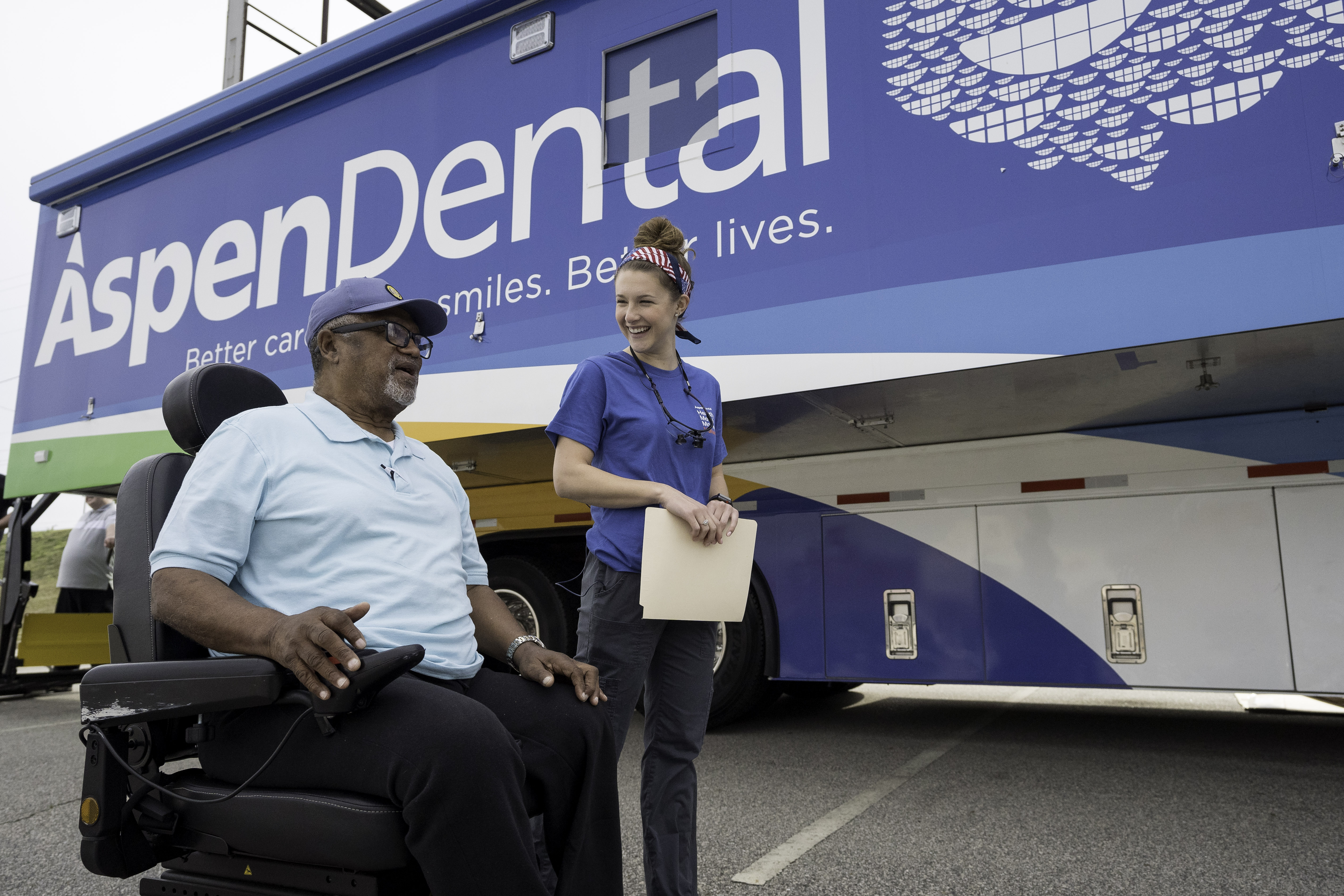 A man in a wheelchair next to a young female dental volunteer in front of the aspen dental mouth mobile bus