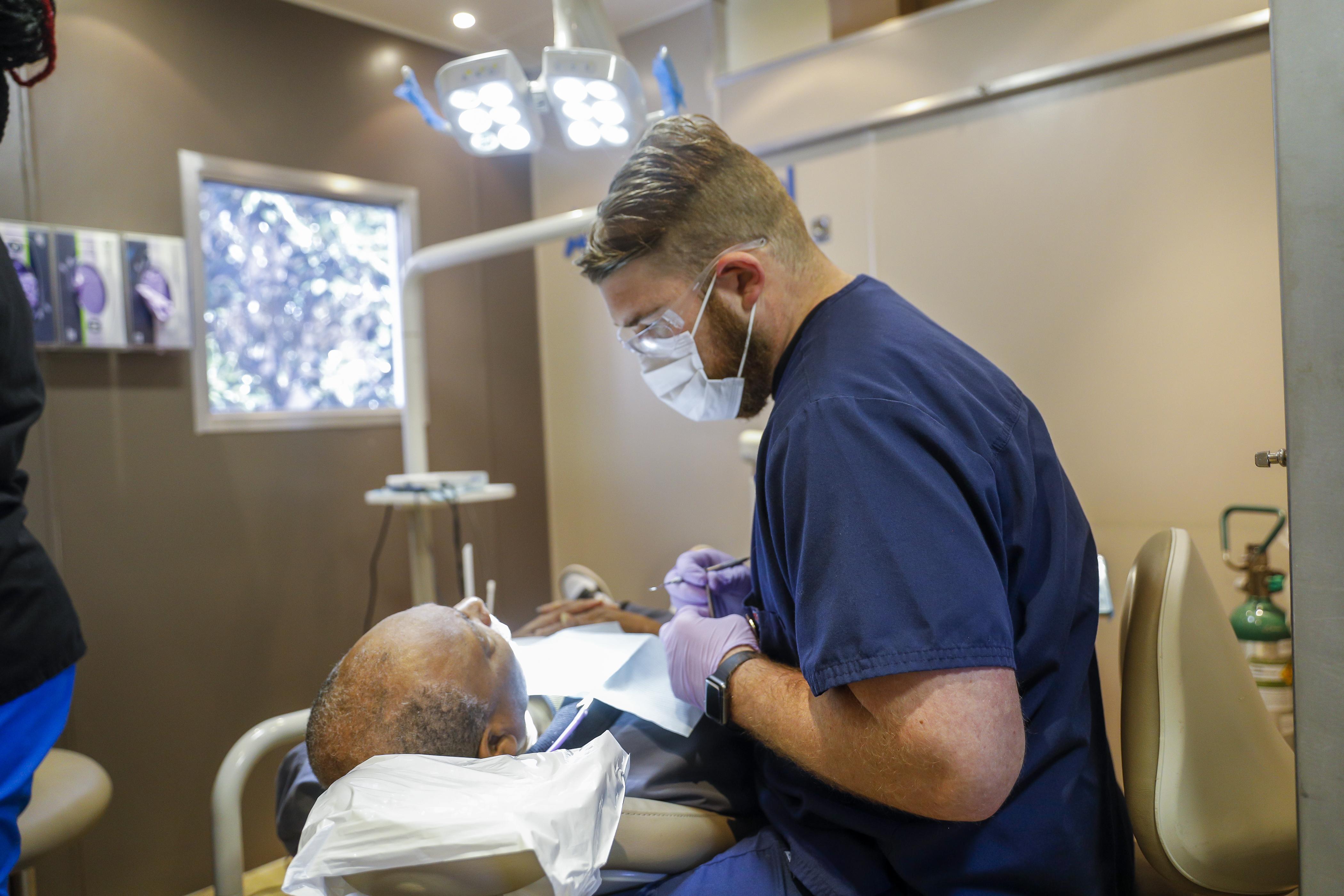 aspen dental staff in ppe overseeing elderly male patient