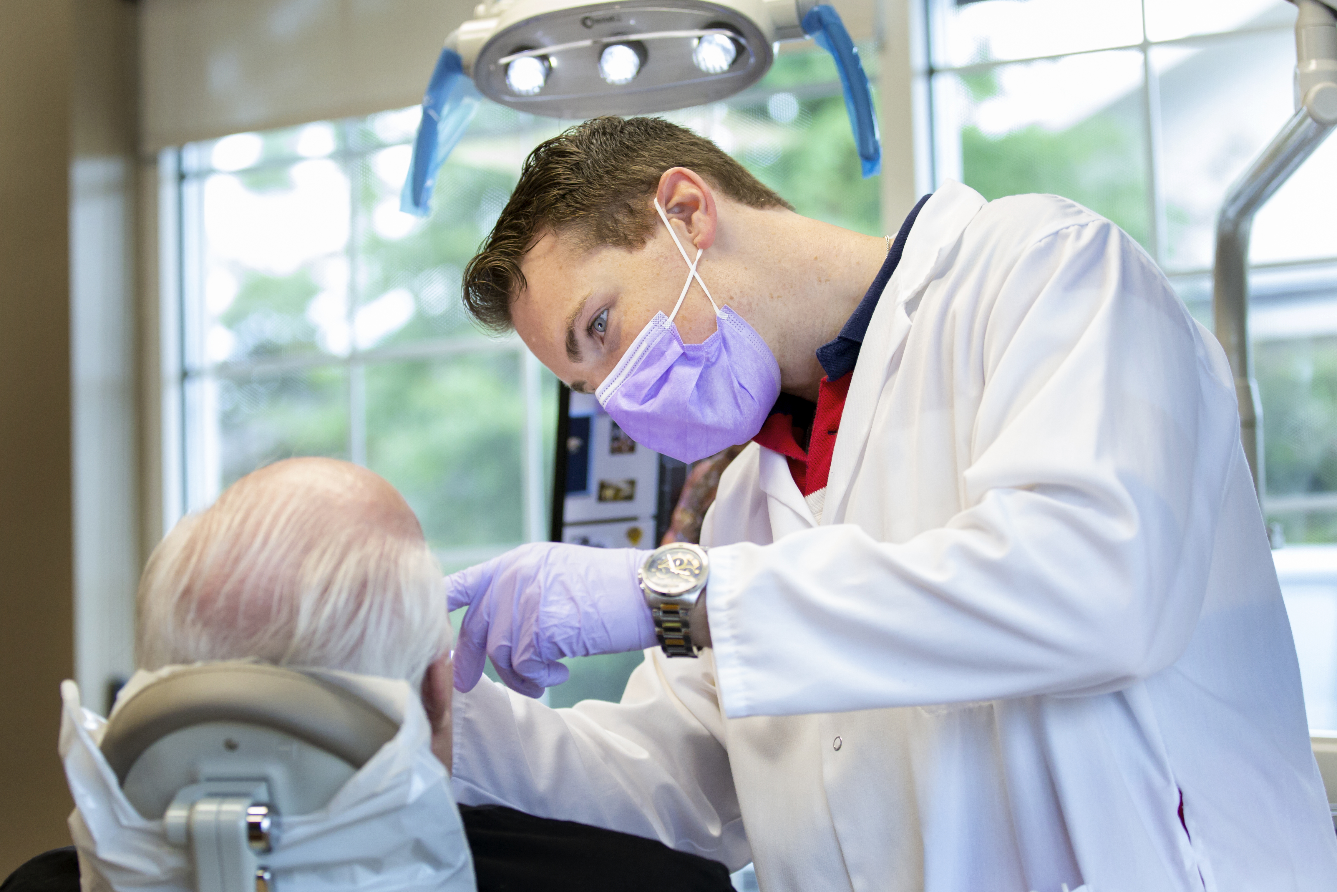 Young Aspen dental employee in PPE examining the mouth of an elderly male patient