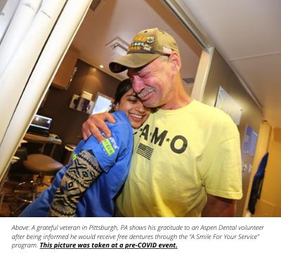 male veteran hugs female dental office worker at a charity event held by aspen dental